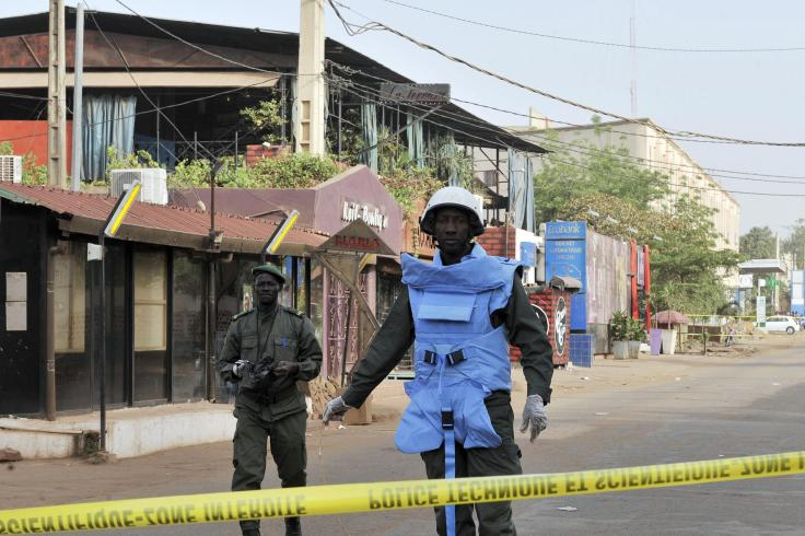 Policemen stand near the La Terrasse restaurant, as seen in the background with the blue curtains, in Bamako, Mali on Saturday.